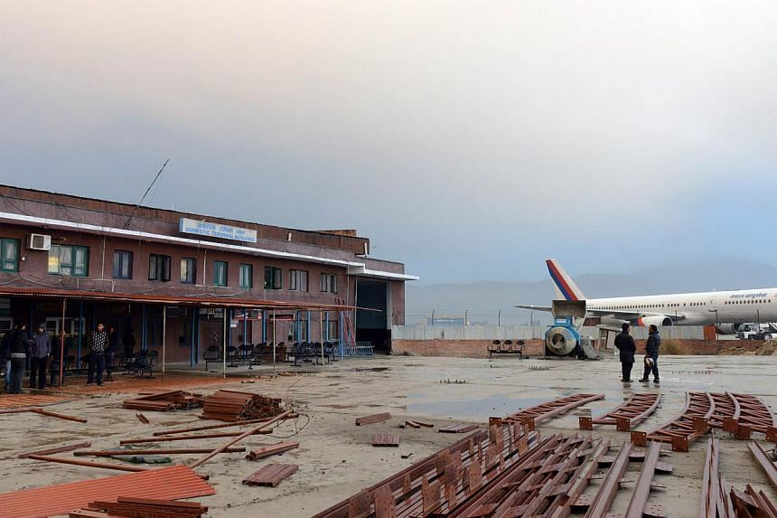 Nepalese residents stand near the domestic terminal building, after a domestic plane crashed in the north-west of the Kathmandu valley, in Kathmandu on Feb 16, 2014. -- PHOTO: AFP