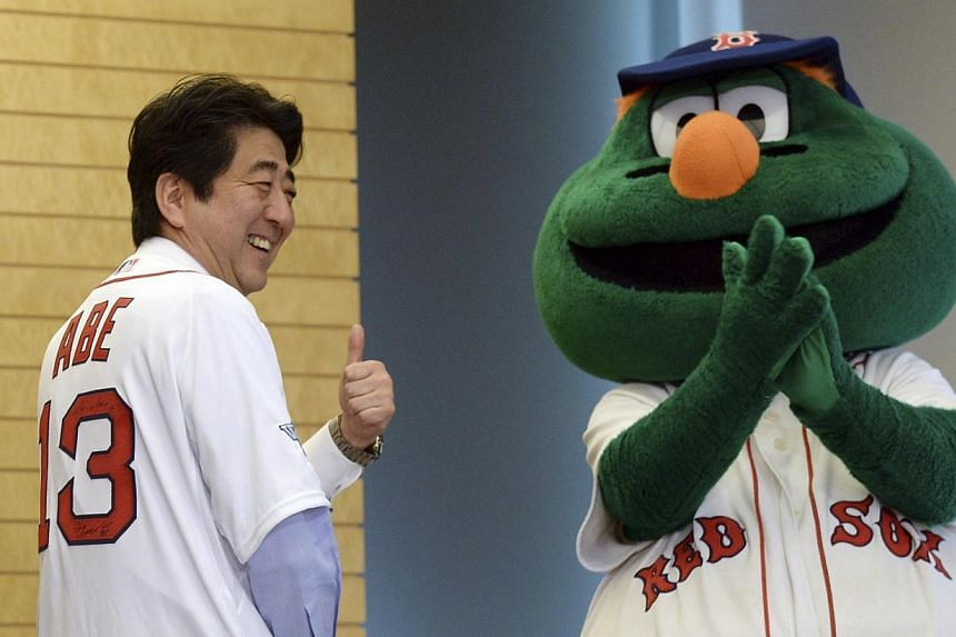 Japan's Prime Minister Shinzo Abe (left) smiles as he wears a Boston Red Soxjersey, while Red Sox mascot Wally looks on at Mr Abe's office in Tokyo, Jan 21, 2014. -- FILE PHOTO: REUTERS