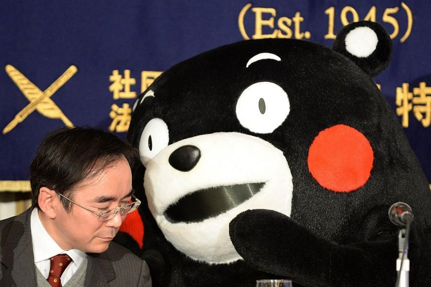 Kumamon gestures to Kumamoto prefecture government brand officerMasataka Naruo during a press conference at the foreign correspondents' club in Tokyo on Feb 14, 2014. -- PHOTO: AFP