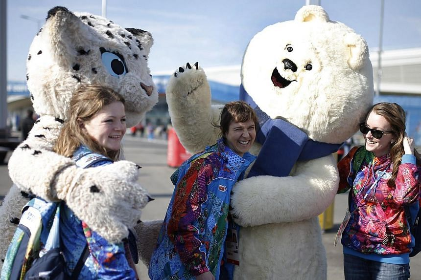 Olympic volunteers pose for photographs with the mascots in the Olympic park during the 2014 Sochi Winter Olympics, Feb 10, 2014. -- FILE PHOTO: REUTERS