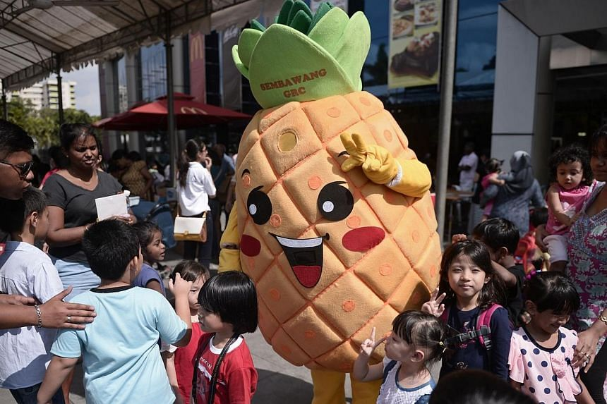 """Children mingle with Mr """"Semba Wang"""", the pineapple mascot which was chosen to represent Sembawang GRC, at the Woodlands Civic Centre on Saturday, Feb 15, 2014. --ST PHOTO:MARK CHEONG"""