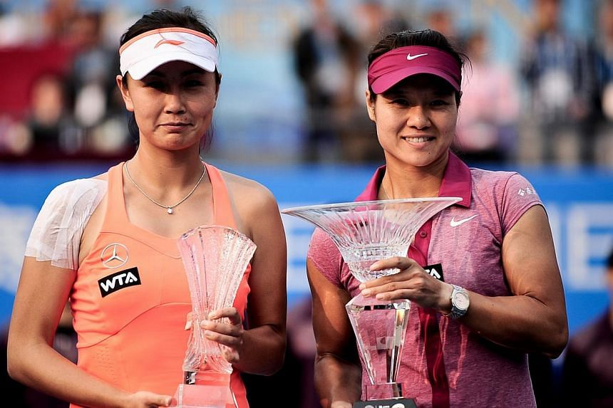 Li Na of China (right) and compatriot Peng Shuai pose with their trophies after the women's singles final match of the WTA Shenzhen Open tennis at Longgang Sports Center in Shenzhen, south China's Guangdong province, on Jan 4, 2014. Li Na moved to an