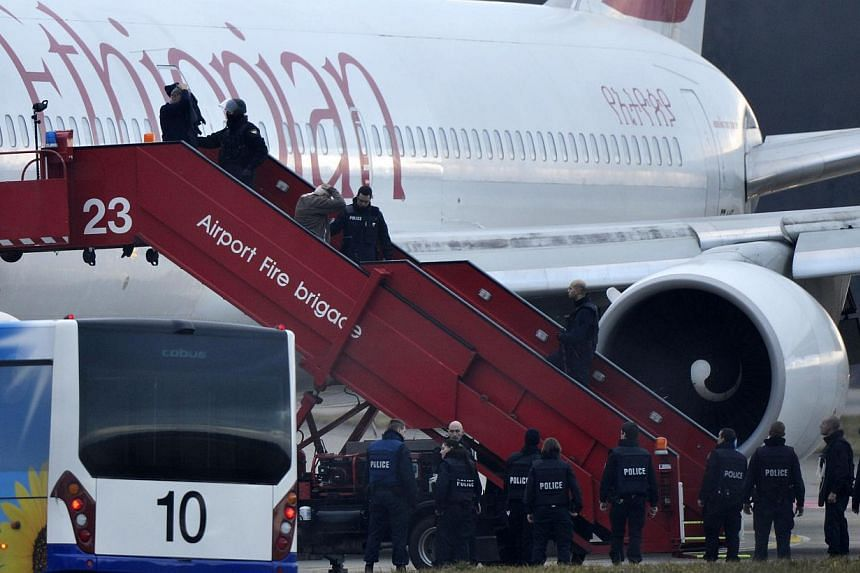 Police evacuate passengers, on Feb 17, 2014, from the Ethiopian Airlines flight en route to Rome, which was on hijacked and forced to land in Geneva, where the hijacker has been arrested, police said.The man who hijacked an Ethiopian Airlines f