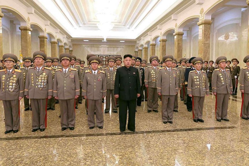 """North Korean leader Kim Jong Un (centre) visits the Kumsusan Palace of the Sun on the 72nd birth anniversary of North Korea's late leader Kim Jong Il in Pyongyang, on Feb 16, 2014. North Korea """"categorically and totally rejects"""" a report into its hum"""