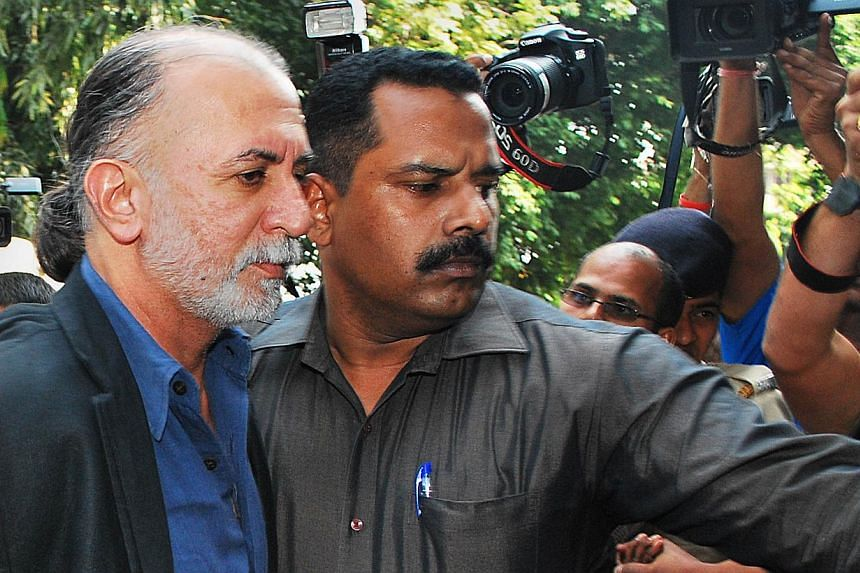 Indian magazine editor, Tarun Tejpal (left), is escorted by police officials from a courthouse after being remanded in police custody in Panaji, on Dec 1, 2013.Indian police on Monday, Feb 17, 2014, formally charged the former news magazine edi