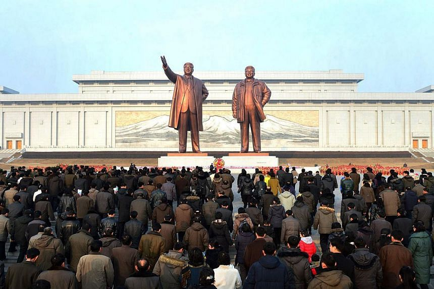 This picture taken on Feb 16, 2014, by North Korea's official Korean Central News Agency (KCNA) shows North Korean people offering flower bouquets to the statues of late leaders Kim Il Sung (left) and Kim Jong Il at Mansu Hill in Pyongyang for the 72