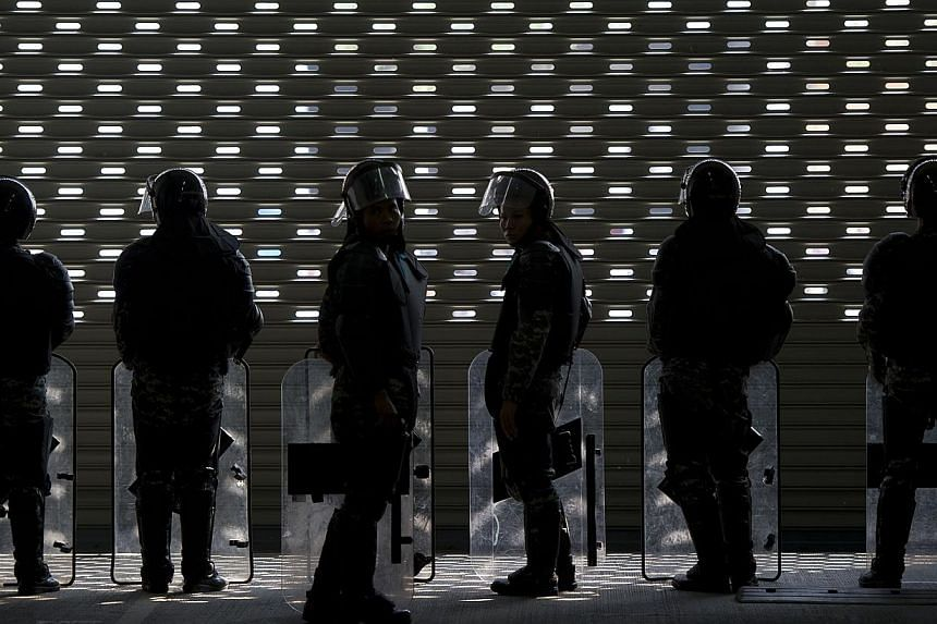 Thai soldiers stand guard during a protest against the government's repeatedly delayed payments for rice submitted to the pledging scheme at the government's temporary office in Bangkok on Feb 17, 2014.Thailand's economy grew 0.6 per cent in th