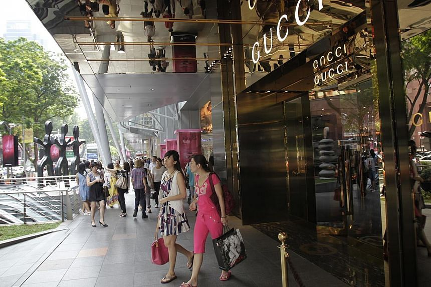 Two Chinese tourists leaving the Gucci outlet at Paragon.Singapore welcomed a record 15.5 million tourists last year, with arrivals rising 7.2 per cent from 2012. -- ST FILE PHOTO:KEVIN LIM