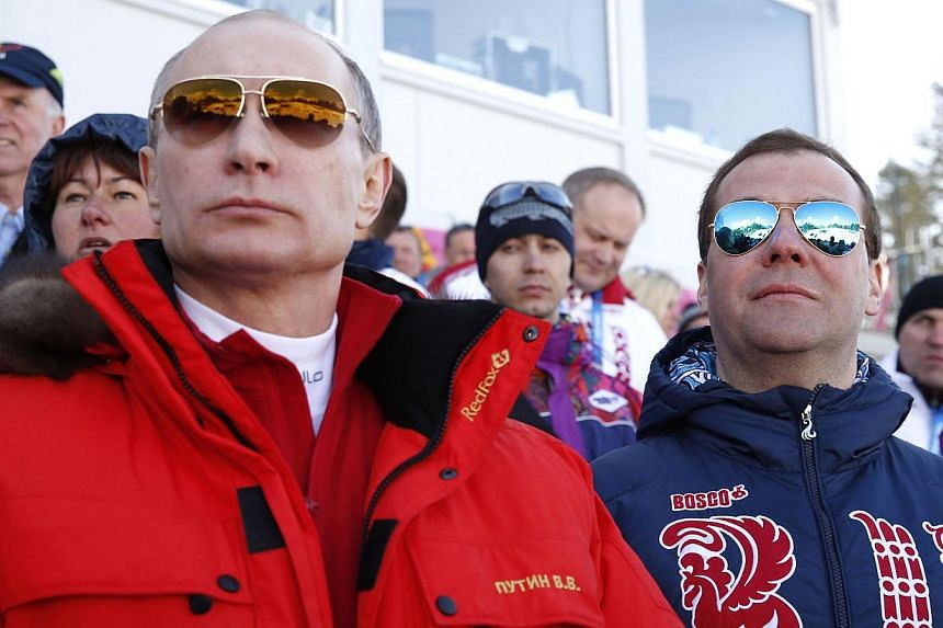 Russia's President Vladimir Putin (left) and Prime Minister Dmitry Medvedev watch the men's cross-country 4 x 10 km relay event at the 2014 Sochi Winter Olympics on Feb 16, 2014. Mr Vladimir Putin says sport and politics do not mix but his actions at