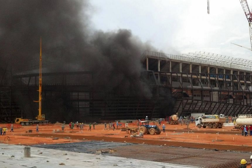 Smoke billows from the partially-constructed Arena Pantanal soccer stadium, projected to host 2014 World Cup matches, from a fire in the base of the structure, in Cuiaba, on Oct 25, 2013.World Cup preparations are on target at the venue o