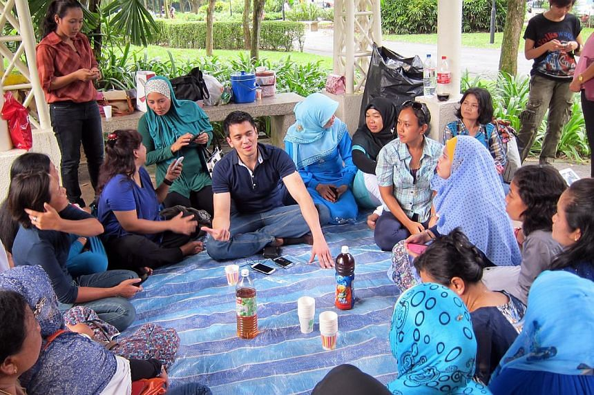 Mr Yoga Dirga Cahya spending time at the Botanic Gardens with some Indonesian maids and volunteer Yatik (in blue tudung), on Sunday. He regularly comes to Singapore to talk with them (above) about their concerns ahead of their country's general ele