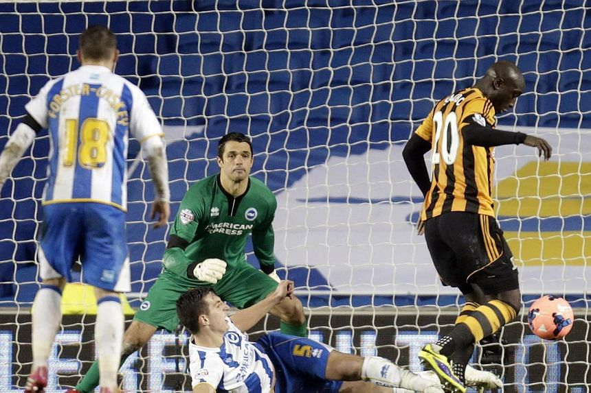Hull City's Yannick Sagbo (right) shoots and scores during their English FA Cup soccer match against Brighton Hove Albion at the Falmer Stadium in Brighton, southern England, on Feb 17, 2014. -- PHOTO: REUTERS
