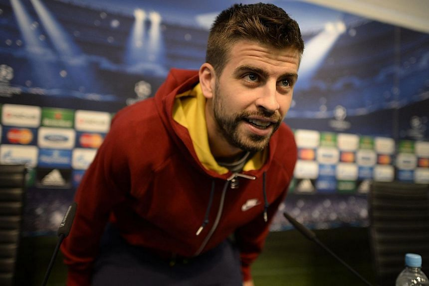 Barcelona's Gerard Pique arrives for a news conference at the Etihad Stadium in Manchester, northern England, on Feb 17, 2014. -- PHOTO: REUTERS
