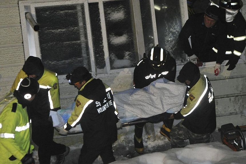 Rescue workers carry a body of a university student trapped by debris from the collapsed resort in Gyeongju, south of Seoul, in this Feb 17, 2014. Photo courtesy of News1. -- PHOTO: REUTERS