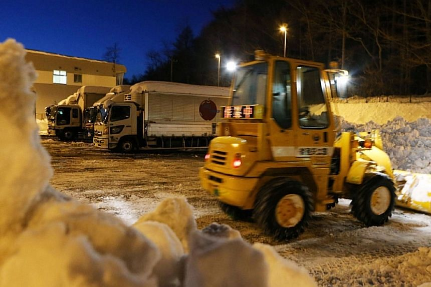 A bulldozer sweeps snow from the road as trailers are stuck at a parking in Karuizawa in Nagano prefecture, central Japan on Feb 17, 2014. -- PHOTO: AFP