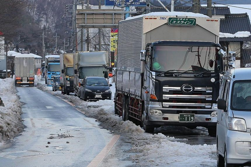 Trucks and vehicles are stuck on the road of National Route 18 in Annaka city in Gunma prefecture on Feb 17, 2014. -- PHOTO: AFP