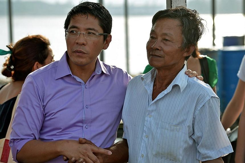 Minister of Statefor National Development Maliki Osman consoling fish farmer Mr Goh Joo Hiang, 60, as he visits coastal fish farmers along the East Johor Straits off the Changi Point jetty affected by recent mass fish deaths.Fish farmers