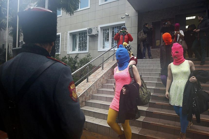 Masked members of Pussy Riot leave a police station in Adler during the 2014 Sochi Winter Olympics, Feb 18, 2014.-- PHOTO: REUTERS