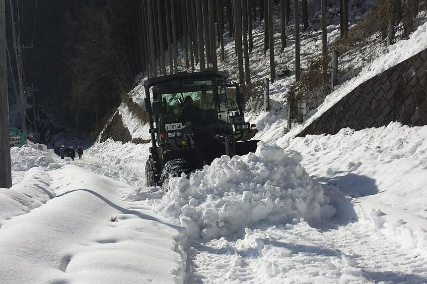 A grader of the Japan Ground Self-Defence Force removes snow covering a public road at Hinohara village, west of Tokyo, in this handout picture taken and released on Feb 17, 2014, by the Japan Ground Self-Defense Force. Snow-choked roads cut off thou