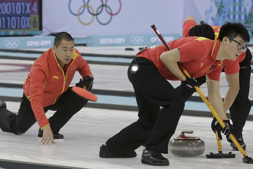 China's skip Liu Rui (left) watches as teammates Zang Jialiang (front right) and Ba Dexin sweep during their men's curling round robin game against Canada in the Ice Cube Curling Centre at the Sochi 2014 Winter Olympic Games on Feb 16, 2014. --