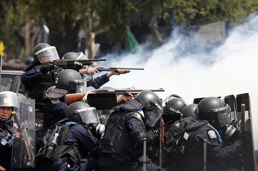Thai policemen aim their weapons towards anti-government protesters during clashes near Bangkok´s Government House on Feb 18, 2014. At least three police officers were wounded as Thai authorities launched an operation to clear anti-government protes