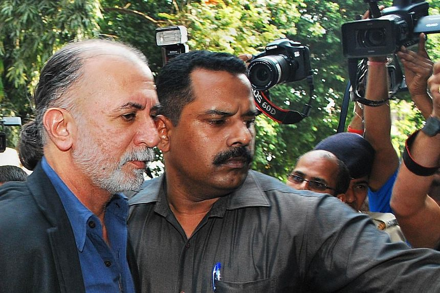 Indian magazine editor Tarun Tejpal is escorted by police officials from a courthouse after being remanded in police custody in Panaji on Dec 1, 2013.  -- FILE PHOTO: AFP