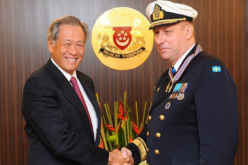 Minister for Defence Ng Eng Hen (left) presenting the Pingat Jasa Gemilang (Tentera) to the Chief of Staff of the Royal Swedish Navy Rear-Admiral Jan Thörnqviston Feb 18, 2014. -- PHOTO: MINDEF