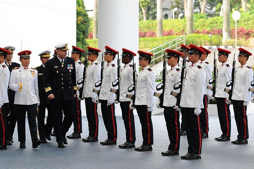 RADM Jan Thörnqvist (in dark uniform) inspecting a Guard of Honour at the Ministry of Defence on Feb 18, 2014. -- PHOTO: MINDEF