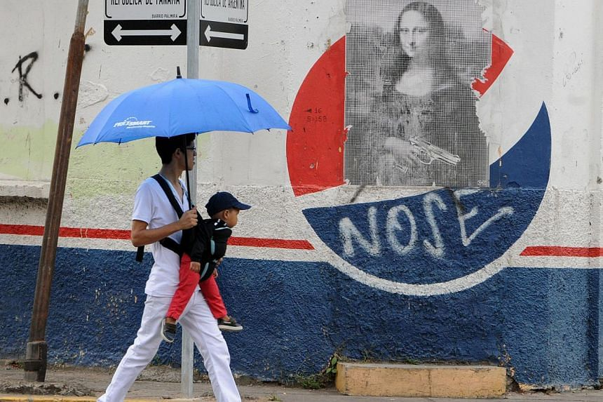 A man looks at a poster of Leonardo da Vinci's Mona Lisa with a gun added to it, as he walks along a street of Tegucigalpa, on Feb 14, 2014. The murder rate in Honduras - the world's highest at more than eight times the international average - has ac