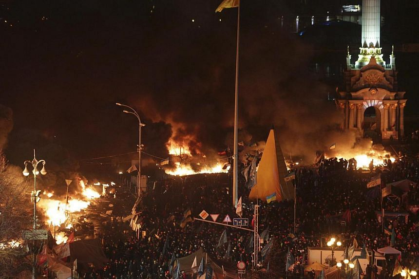 Anti-government protesters gather near fires at a tent encampment during clashes with riot police in Independence Square in Kiev on Feb 19, 2014. -- PHOTO: REUTERS