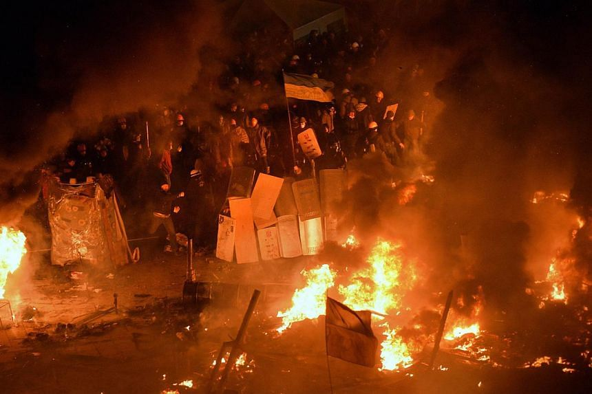 Anti-government protesters clash with the police during their storming of Independence Square in Kiev on Feb 18, 2014. -- PHOTO: AFP