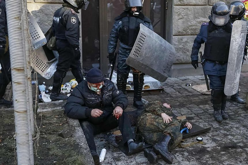 Riot police stand near wounded people after clashes in central Kiev on Feb 18, 2014. -- PHOTO: REUTERS