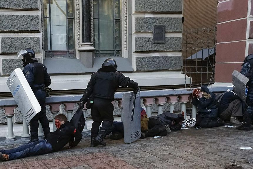 Riot policemen detain wounded people after clashes in central Kiev on Feb 18, 2014. -- PHOTO: REUTERS