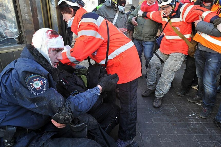 Red Cross workers give first aid to policemen wounded during clashes with anti-government protester in Kiev on Feb 18, 2014. -- PHOTO: AFP