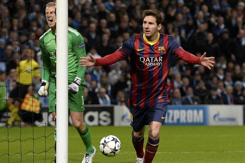 Barcelona's Lionel Messi (right) celebrates after scoring a penalty past Manchester City's goalkeeper Joe Hart (left) during their Champions League round of 16 first leg soccer match at the Etihad Stadium in Manchester, northern England, on Feb 18, 2