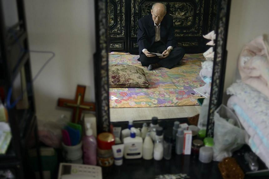Mr Kim Se Rin is reflected in a mirror as he sits on his bed looking at photos of his South Korean family, prepared ahead of a meeting with relatives in the North, at his home on the outskirts of Seoul on Feb 17, 2014. -- FILE PHOTO: AFP