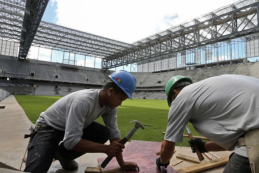 Workers are pictured inside the Arena da Baixada soccer stadium as it is being built to host matches of the 2014 World Cup in Curitiba, on Feb 17, 2014. Fifa handed a World Cup reprieve to the Brazilian city of Curitiba on Tuesday, barely one month a