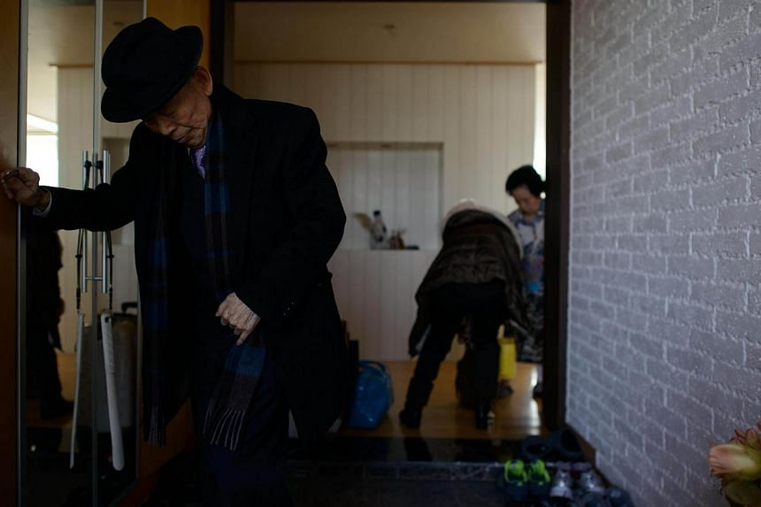 North Korean-born Kim Se Rim (left) leaves his house in Seoul as he prepares to make his way to a reunion of families from North and South Korea seperated by the war on Feb 19, 2014. -- PHOTO: AFP