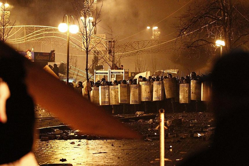 Riot policemen approaching anti-government protesters during clashes at the Independence Square in Kiev on Feb 18, 2014. -- PHOTO: REUTERS