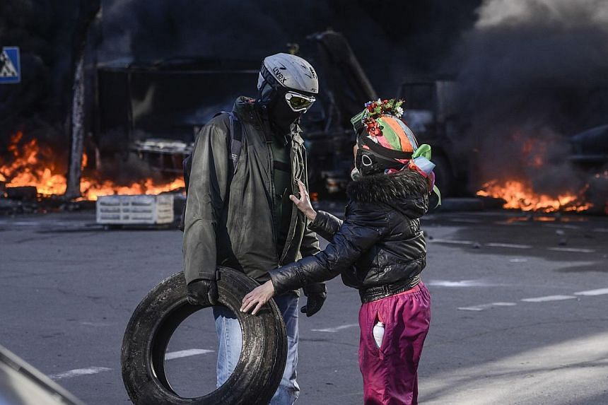 People speak near a barricade on fire during clashes between anti-government protesters and Interior Ministry members in Kiev, Feb 18, 2014. -- PHOTO: REUTERS
