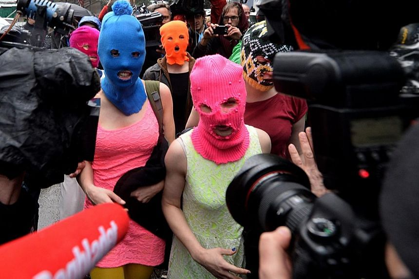 Wearing masks members of Russian punk group Pussy Riot, Nadezhda Tolokonnikova (left) and Maria Alyokhina (right) speak to journalists while leaving the police station of Adler, near Sochi, on Feb 18, 2014, after her arrest earlier in the host city o
