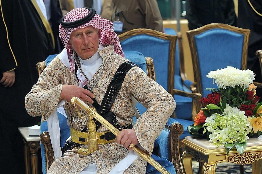 Britain's Prince Charles, wearing a traditional Saudi attire, attends the traditional Saudi dance, known as 'Arda', which was performed during Janadriya culture festival at Der'iya in Riyadh, Feb 18, 2014. -- PHOTO: REUTERS