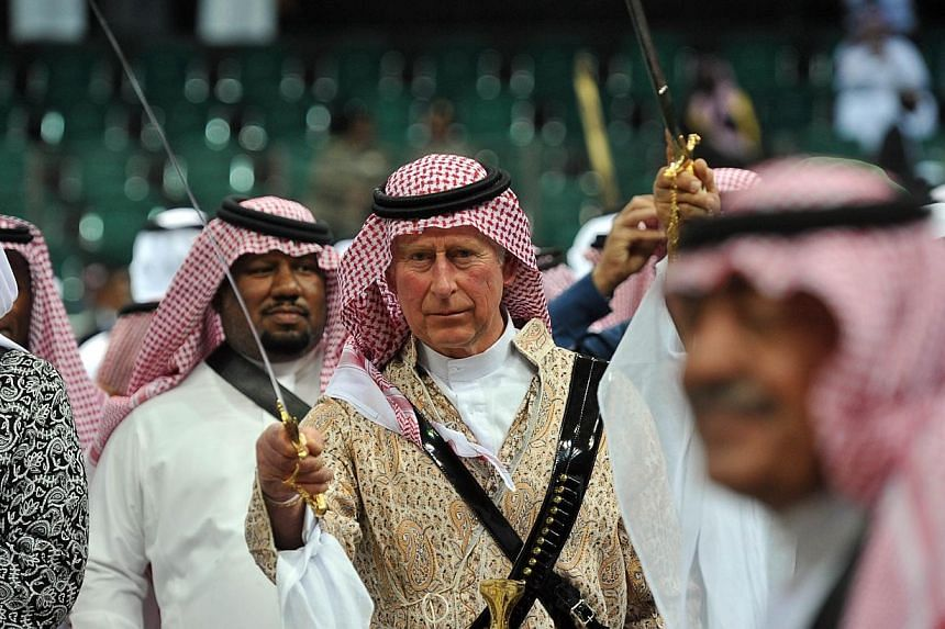 Britain's Prince Charles (centre) wearing traditional Saudi uniform, dances with sword during the traditional Saudi dancing best known as 'Arda' performed during Janadriya culture festival at Der'iya in Riyadh, on Feb 18, 2014. -- PHOTO: AFP