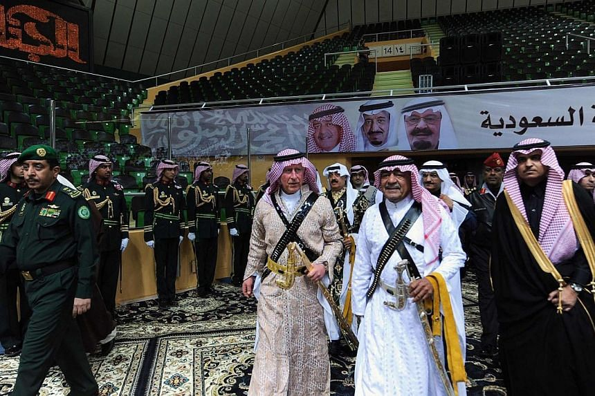"""Saudi Arabia's second deputy Prime Minister Muqrin bin Abdulaziz (front second right) escorts Britain's Prince Charles (centre) upon their arrival to participate in the traditional Saudi dance known as """"Arda"""" during the Janadriya culture festival at"""