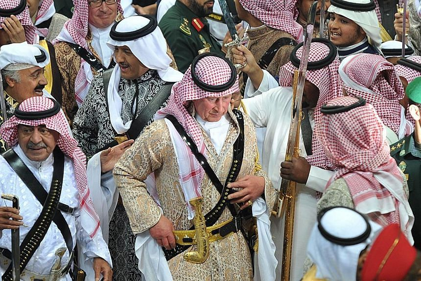 Britain's Prince Charles (centre), wearing a traditional Saudi costume, walks with Saudi's second deputy Prime Minister Mugren bin Abdulaziz (bottom left) as they are surrounded by unidentified Saudi Emirs after the end of the traditional Saudi danci