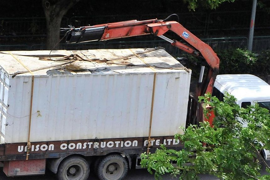 The beam of a crane carried by a trailer went through the windscreen of a car on the Pan Island Expressway on Oct 29, 2011.A lorry driver who caused a crane boom to hit an overhead bridge along an expressway was jailed for one week and banned f