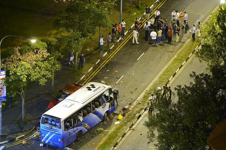 """The wrecked private bus at the junction of Race Course Road at the aftermath of the Little India riot on Dec 9, 2013.Accident reconstruction expert Dr Michael Tay wrapped up his evidence on Wednesday, Feb 19, 2014, on the """"combination of factor"""
