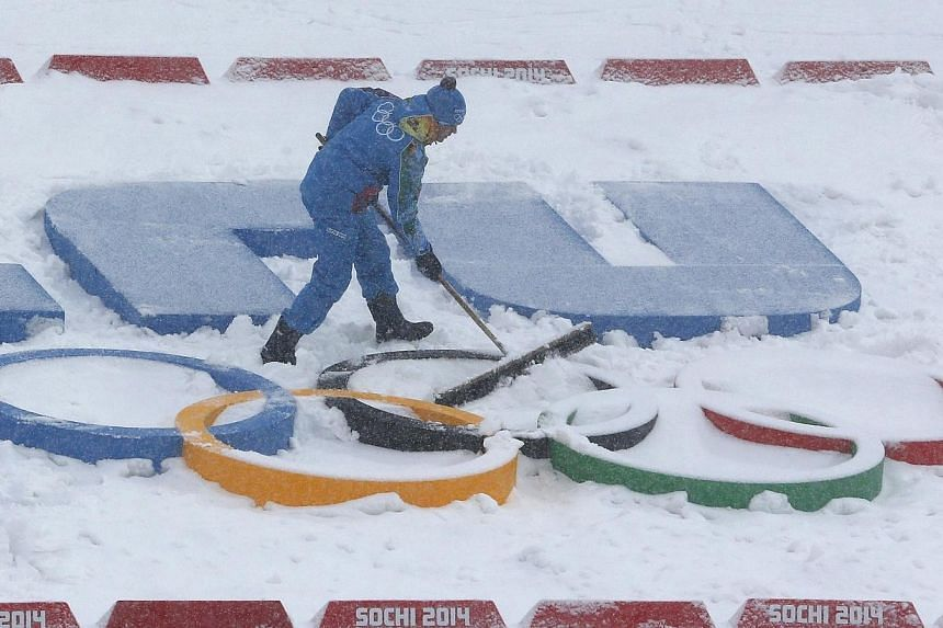 A worker clears the snow from the Olympic rings before the start of the men's biathlon 15km mass start event at the Sochi 2014 Winter Olympic Games in Rosa Khutor on Feb 18, 2014.The International Olympic Committee (IOC) said on Wednesday it is