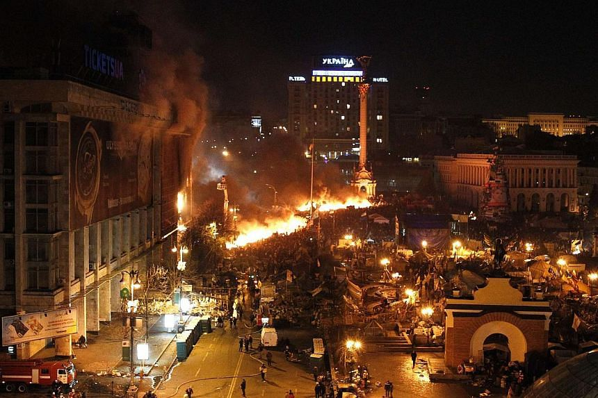 Kiev's occupied Independence Square was engulfed in flames on early Wednesday, Feb 19, 2014, as police stormed the main protest camp in a bloody escalation of Ukraine's three-month political crisis which left at least 16 people dead. -- PHOTO: REUTER