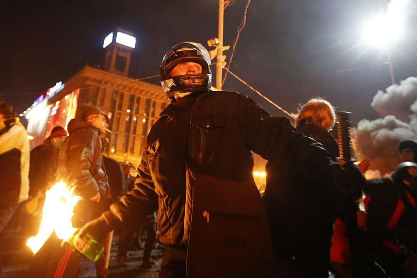 An anti-government protester prepares to throw a petrol bomb during clashes with riot police at Independence Square in Kiev on Feb 18, 2014. Ukrainian riot police advanced on Tuesday onto a central Kiev square occupied by protesters, after at least 1